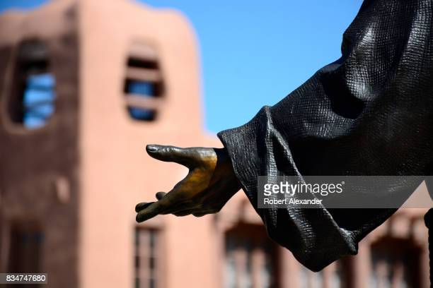 A bronze statue of St Francis of Assisi with his outreached hand stands in front of The Cathedral Basilica of St Francis of Assisi commonly known as...