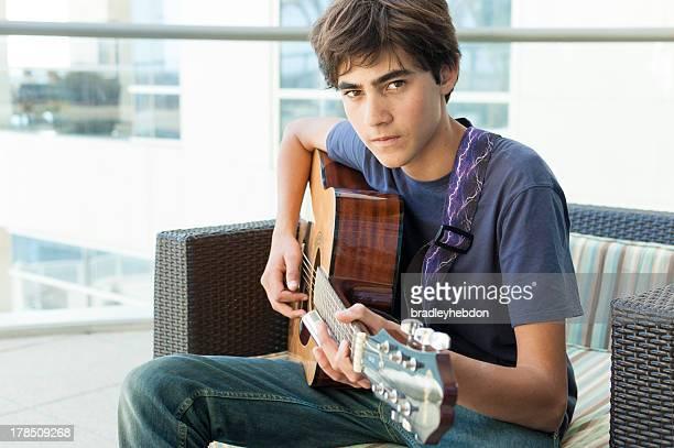 Brooding un adolescente ragazzo Suona la chitarra acustica
