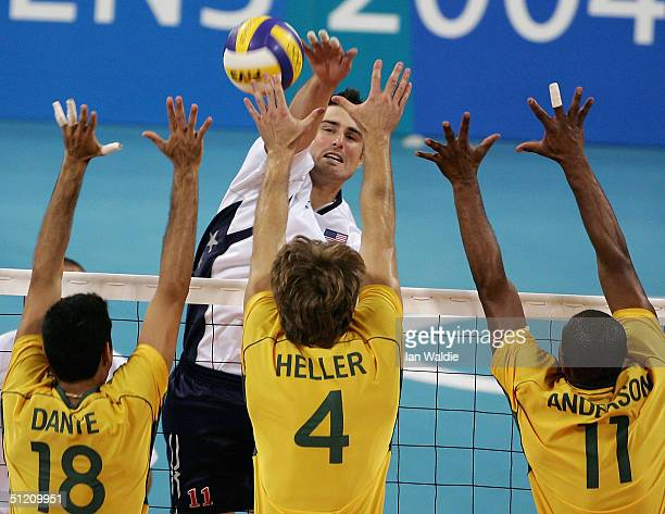 Brook Billings of the USA spikes the ball past Dante Guimaraes Amaral Andre Heller and Anderson Rodrigues of Brazil at the men's indoor Volleyball...