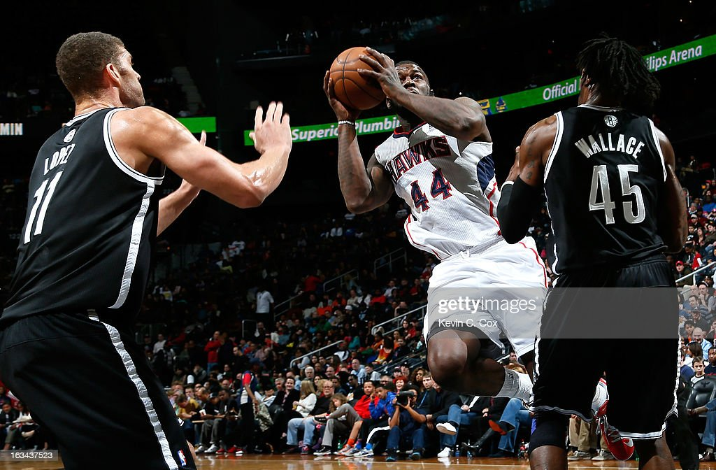 Brook Lopez #11 and <a gi-track='captionPersonalityLinkClicked' href=/galleries/search?phrase=Gerald+Wallace&family=editorial&specificpeople=202117 ng-click='$event.stopPropagation()'>Gerald Wallace</a> #45 of the Brooklyn Nets defend against Ivan Johnson #44 of the Atlanta Hawks at Philips Arena on March 9, 2013 in Atlanta, Georgia.