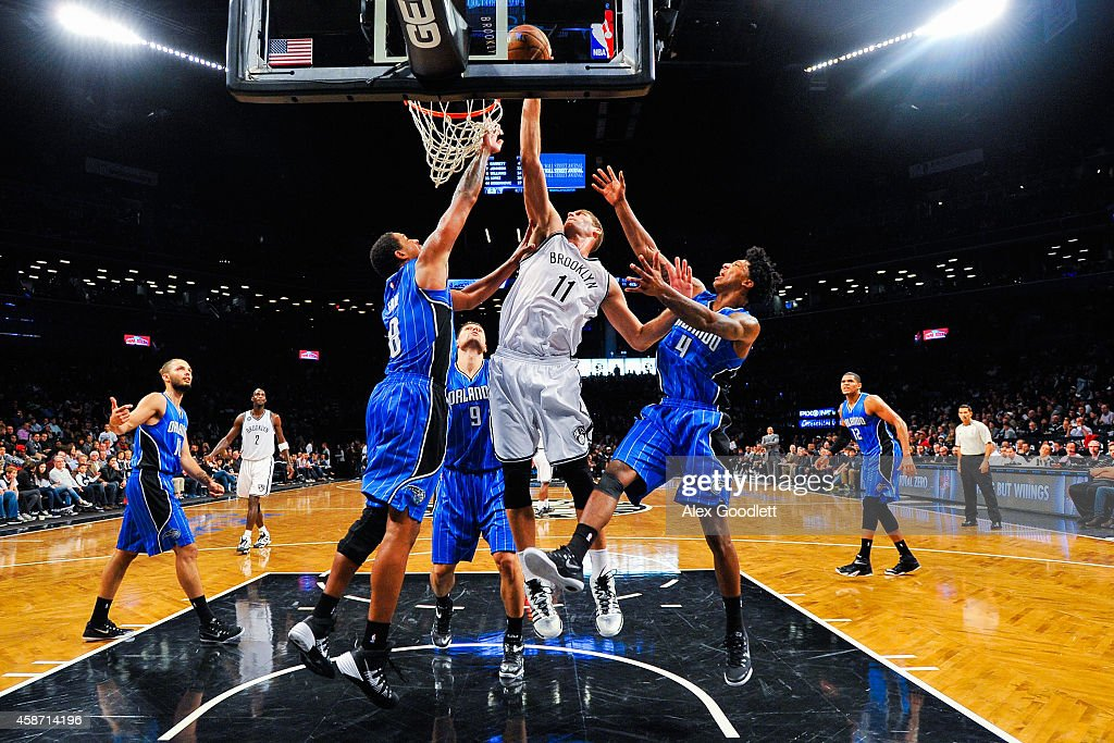 Brook Lopez #11 of the Brooklyn Nets attempts a shot over Channing Frye #8 and Elfrid Payton #4 of the Orlando Magic in the second half at the Barclays Center on November 9, 2014 in the Brooklyn borough of New York City.