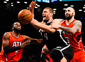 Brook Lopez of the Brooklyn Nets attempts to drive past Pero Antic and DeMarre Carroll of the Atlanta Hawks during the first round of the 2015 NBA...