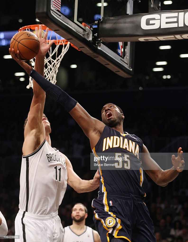 Brook Lopez #11 of the Brooklyn Nets blocks a shot by Roy Hibbert #55 of the Indiana Pacers in the fourth quarter at the Barclays Center on January 13, 2013 in New York City.