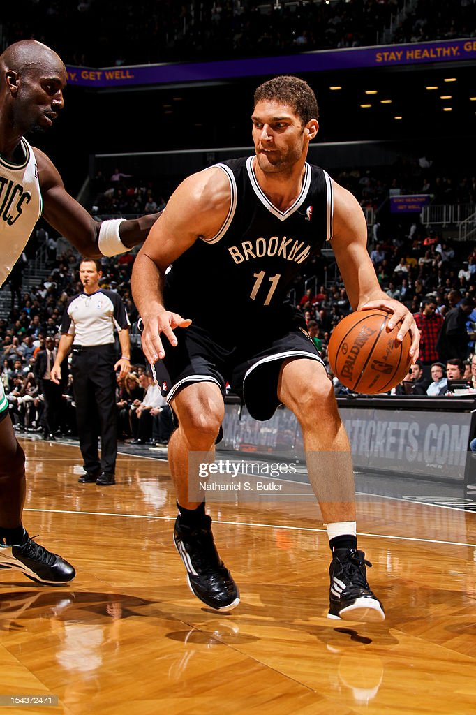 Brook Lopez #11 of the Brooklyn Nets drives against Kevin Garnett #5 of the Boston Celtics during a pre-season game on October 18, 2012 at the Barclays Center in the Brooklyn borough of New York City.