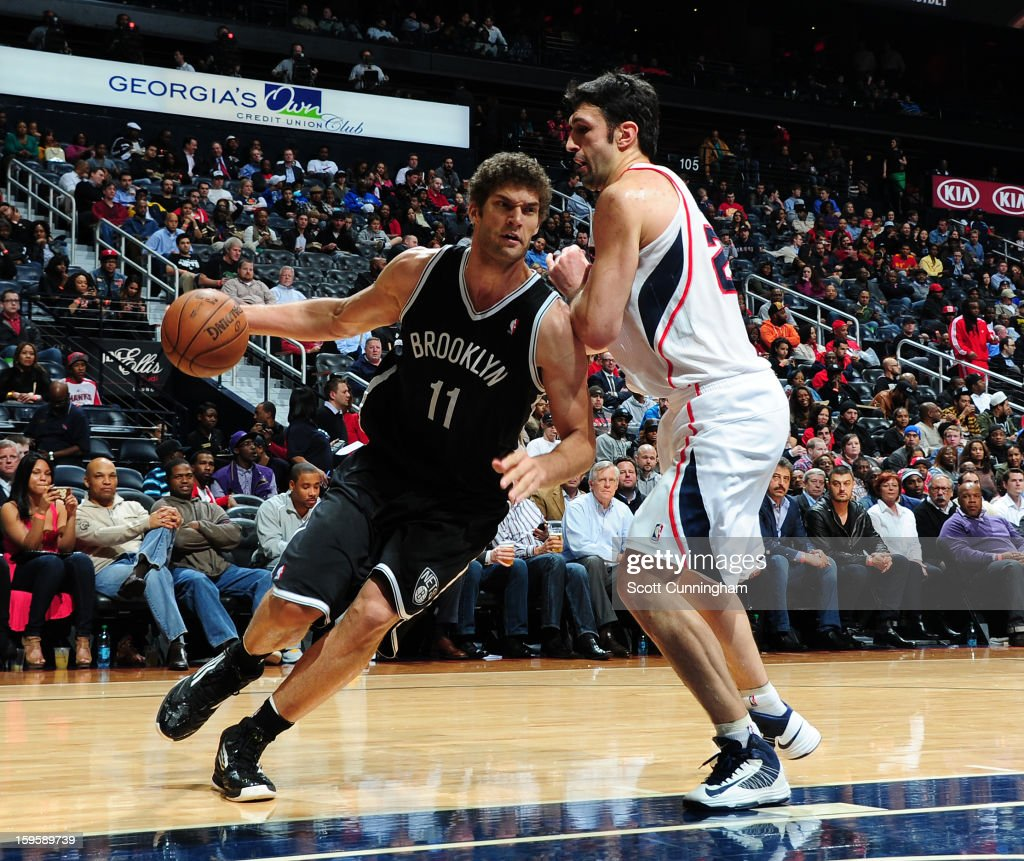 Brook Lopez #11 of the Brooklyn Nets drives to the basket against Zaza Pachulia #27 of the Atlanta Hawks on January 16, 2013 at Philips Arena in Atlanta, Georgia.
