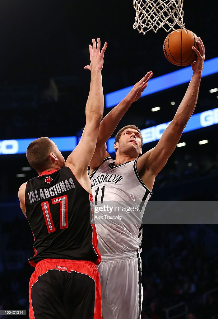 Brook Lopez #11 of the Brooklyn Nets goes to the basket as <a gi-track='captionPersonalityLinkClicked' href=/galleries/search?phrase=Jonas+Valanciunas&family=editorial&specificpeople=5654195 ng-click='$event.stopPropagation()'>Jonas Valanciunas</a> #17 of the Toronto Raptors defends at the Barclays Center on November 3, 2012 in the Brooklyn borough of New York City.