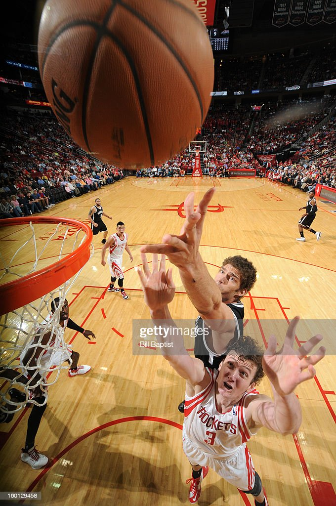 Brook Lopez #11 of the Brooklyn Nets goes up for a rebound against Omer Asik #3 of the Houston Rockets on January 26, 2013 at the Toyota Center in Houston, Texas.
