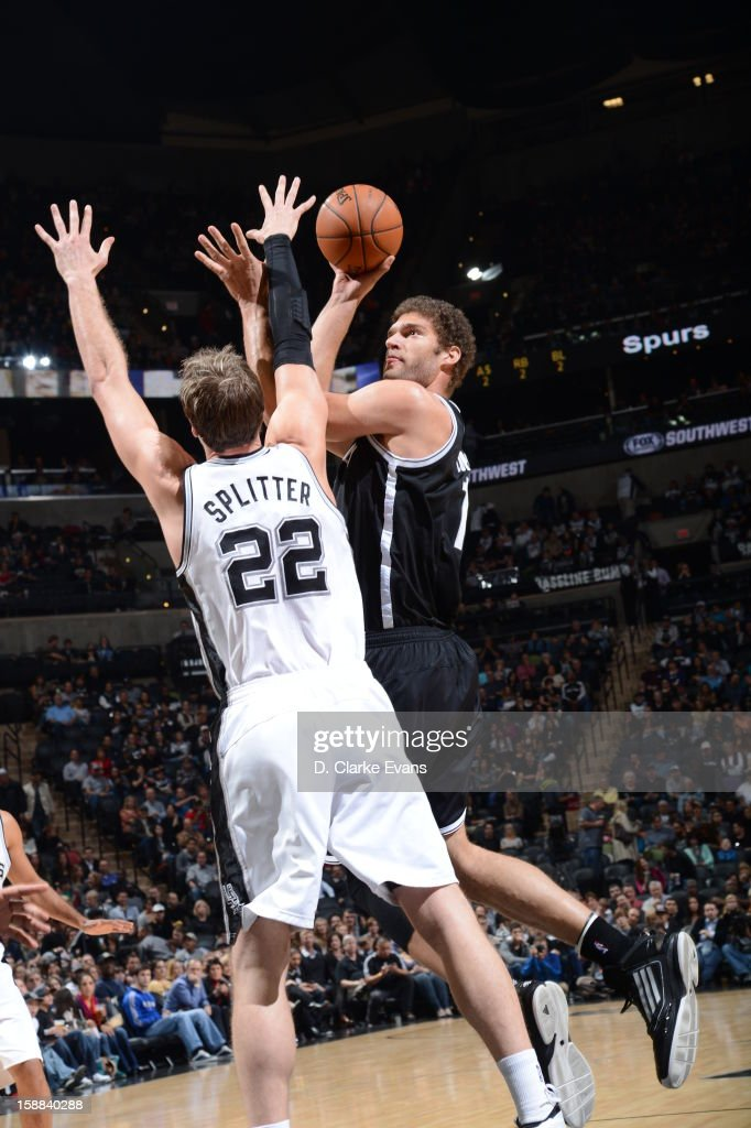 <a gi-track='captionPersonalityLinkClicked' href=/galleries/search?phrase=Brook+Lopez&family=editorial&specificpeople=3847328 ng-click='$event.stopPropagation()'>Brook Lopez</a> #11 of the Brooklyn Nets goes up for a shot against <a gi-track='captionPersonalityLinkClicked' href=/galleries/search?phrase=Tiago+Splitter&family=editorial&specificpeople=208218 ng-click='$event.stopPropagation()'>Tiago Splitter</a> #21 of the San Antonio Spurs on December 31, 2012 at the AT&T Center in San Antonio, Texas.