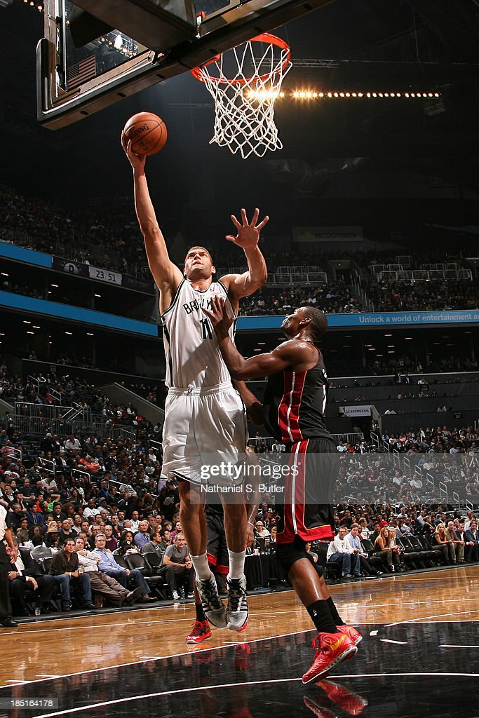 Brook Lopez #11 of the Brooklyn Nets goes up to shoot against Chris Bosh #1 of the Miami Heat during a preseason game at the Barclays Center on October 17, 2013 in the Brooklyn borough of New York City.