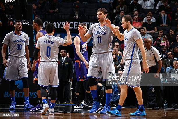 Brook Lopez of the Brooklyn Nets high fives teammates during the game against the Phoenix Suns on December 1 2015 at Barclays Center in Brooklyn New...