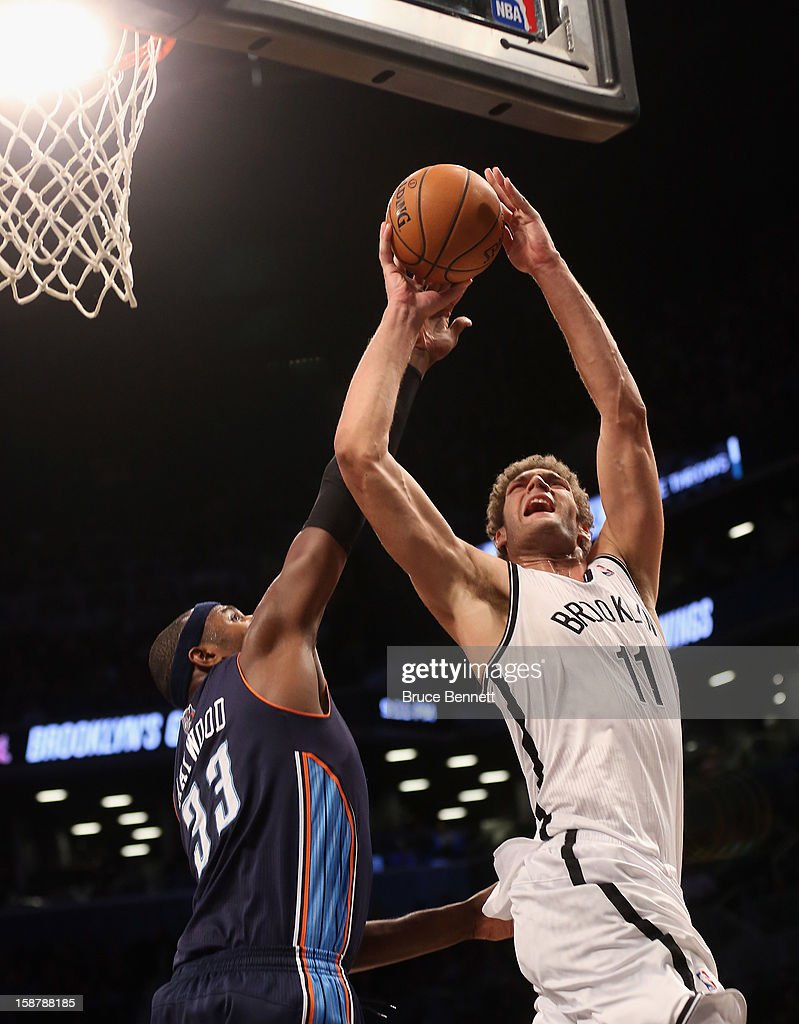 Brook Lopez #11 of the Brooklyn Nets is stopped in the third quarter by Brendan Haywood #33 of the Charlotte Bobcats at the Barclays Center on December 28, 2012 in the Brooklyn borough of New York City.