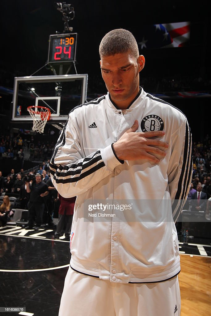 Brook Lopez #11 of the Brooklyn Nets listens to the National Anthem prior to the game against the Denver Nuggets at the Barclays Center on February 13, 2013 in the Brooklyn borough of New York City in New York City.