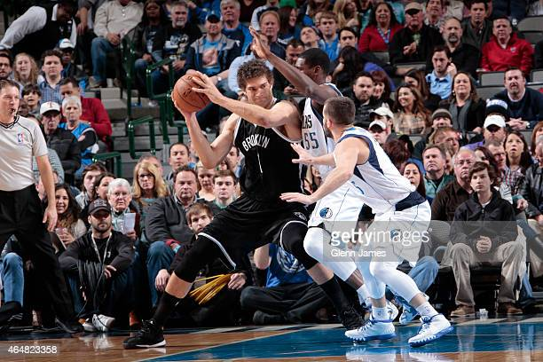 Brook Lopez of the Brooklyn Nets posts up against Bernard James of the Dallas Mavericks on February 28 2015 at the American Airlines Center in Dallas...