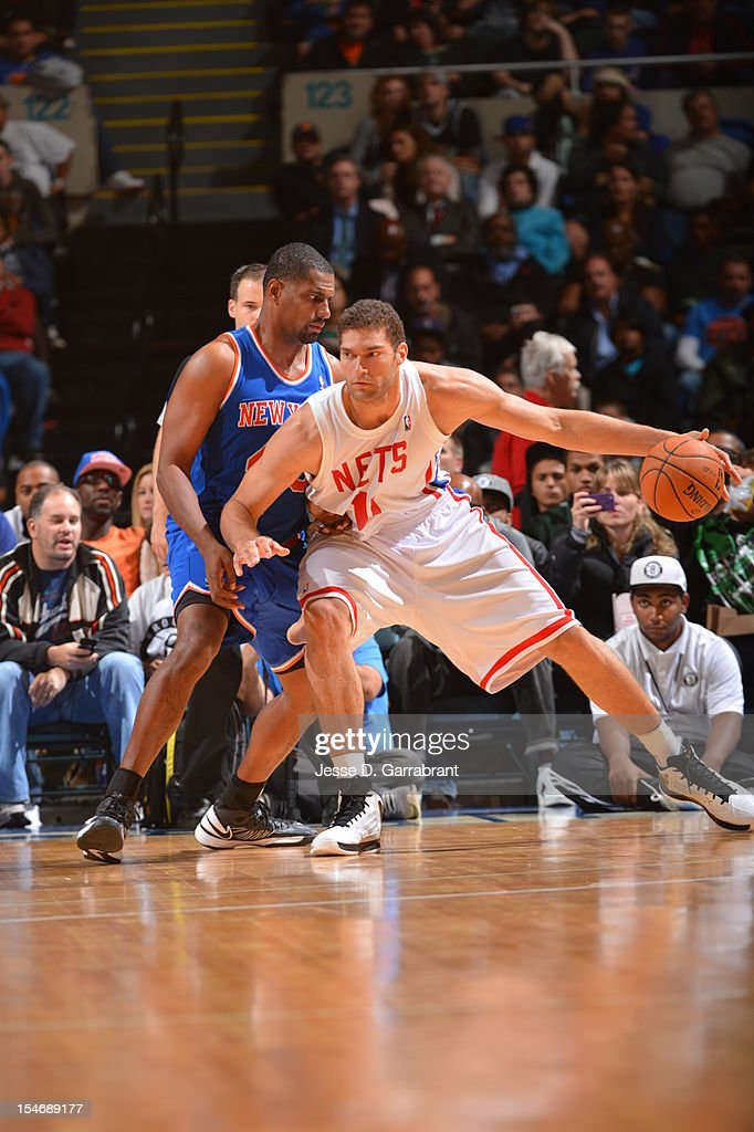 Brook Lopez #11 of the Brooklyn Nets protects the ball against Kurt Thomas #40 of the New York Knicks on October 24, 2012 at the Nassau Veterans Memorial Coliseum in Long Island, New York.