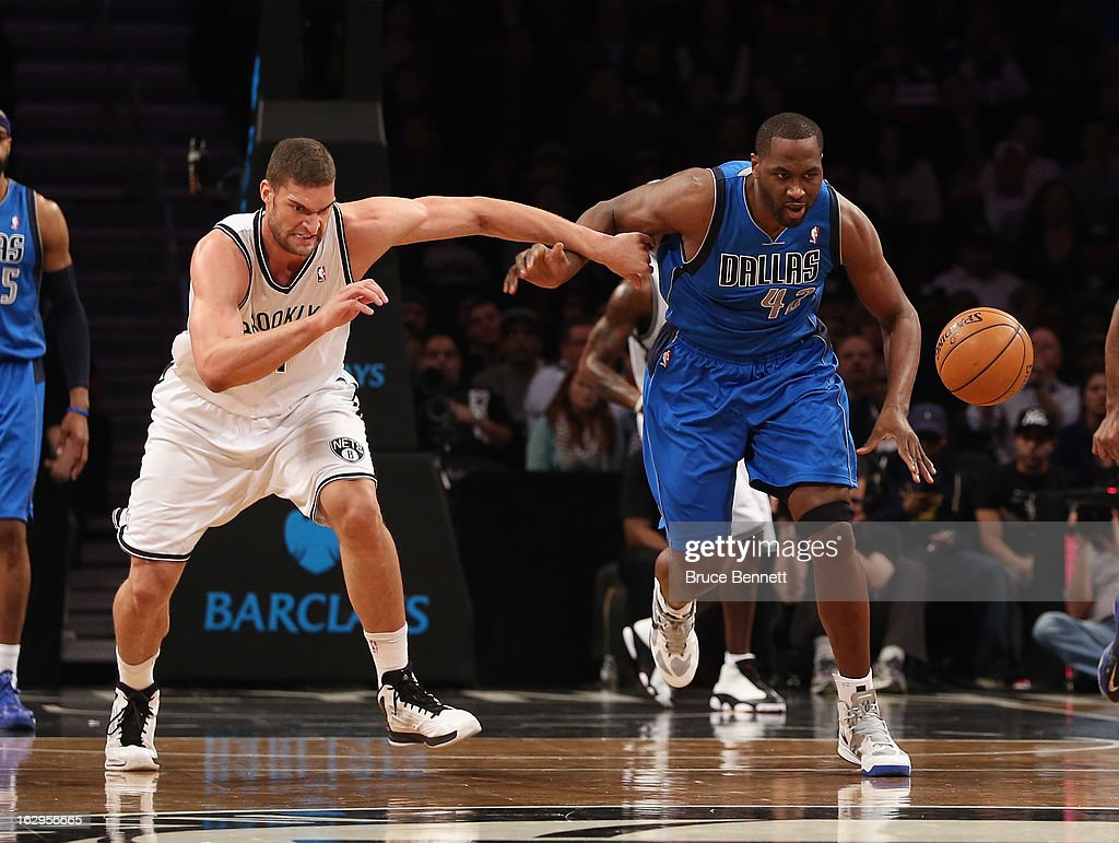 Brook Lopez #11 of the Brooklyn Nets races against Elton Brand #42 of the Dallas Mavericks at the Brooklyn Nets at the Barclays Center on March 1, 2013 in New York City. The Mavericks defeated the Nets 98-90.
