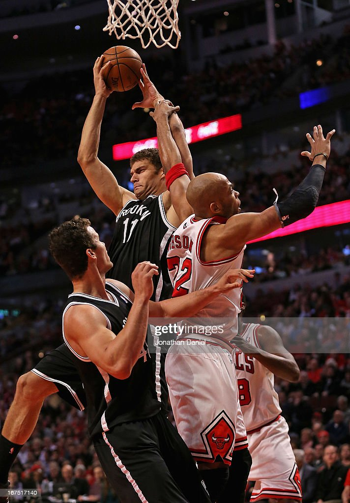 Brook Lopez #11 of the Brooklyn Nets rebounds over teammate Kris Humphries #43 and Taj Gibson #22 of the Chicago Bulls in Game Three of the Eastern Conference Quarterfinals during the 2013 NBA Playoffs at the United Center on April 25, 2013 in Chicago, Illinois. The Bulls defeated the Nets 79-76.