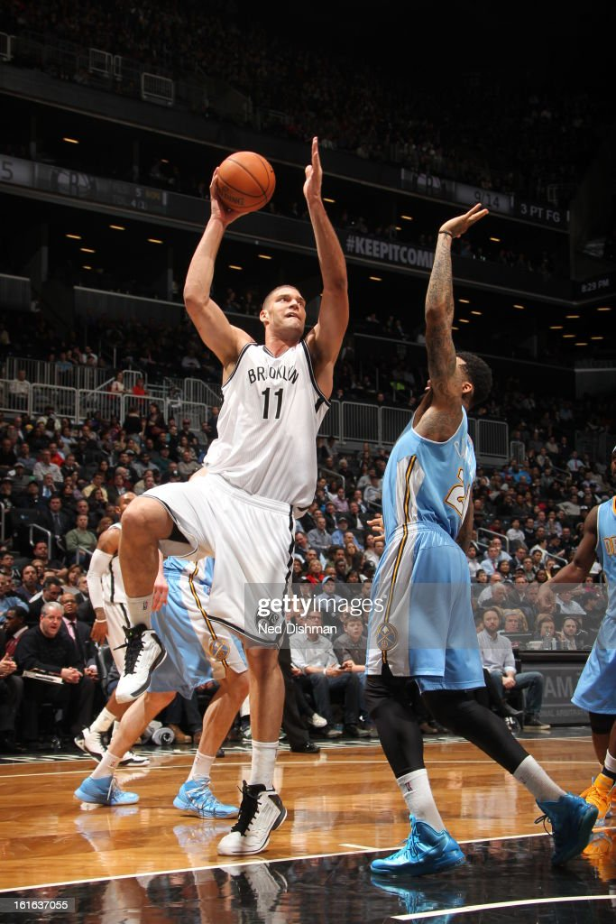 Brook Lopez #11 of the Brooklyn Nets takes a hookshot against the Denver Nuggets at the Barclays Center on February 13, 2013 in the Brooklyn borough of New York City in New York City.