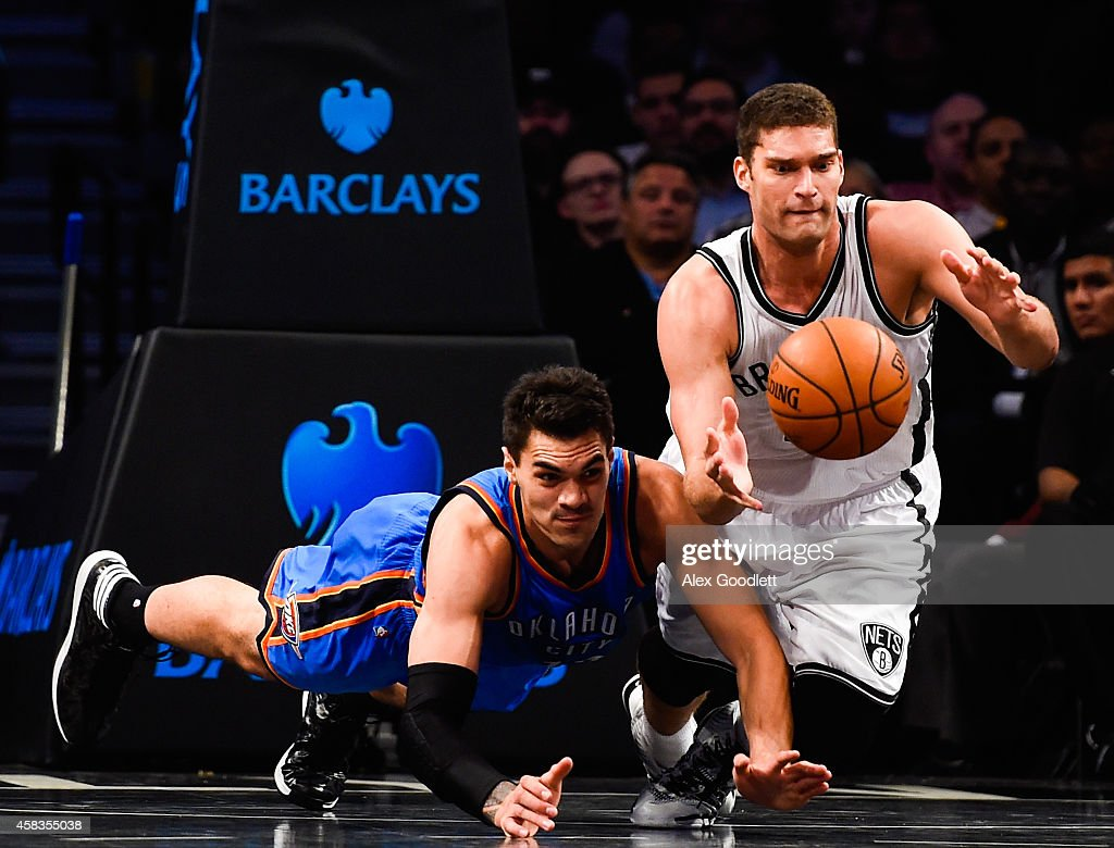 Brook Lopez of the Brooklyn Netsdies for the ball with Steven Adams of the Oklahoma City Thunder in the second half at the Barclays Center on...