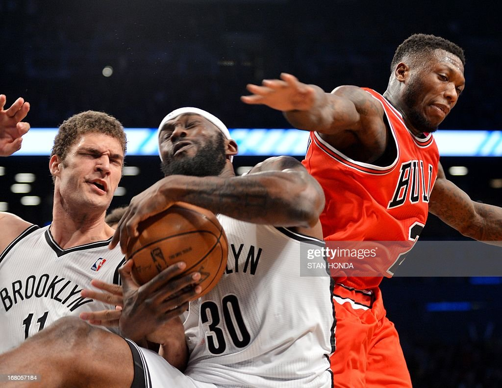 Brook Lopez (L), Reggie Evans (C) of the Brooklyn Nets and Nate Robinson (R) of the Chicago Bulls fight for rebound during Game 7 of the Eastern Conference quarterfinals at the Barclays Center May 4, 2013 in the Brooklyn borough of New York. The Bulls won, 99-93 to advance to the next round of playoffs against the Miami Heat. AFP PHOTO/Stan HONDA