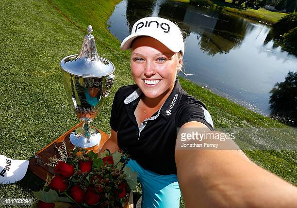 Brooke Henderson of Canada imitates a selfie with the trophy after her 21 strokes under par victory during the final round of the LPGA Cambia...