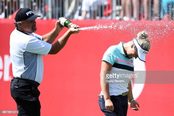 Brooke Henderson of Canada is sprayed with champagne by her father Dave Henderson during the final round of the Meijer LPGA Classic at Blythefield...
