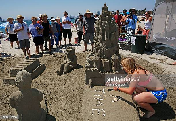 Brooke James right places shells in letters on the amateur sand sculpture 'PopUp Book' by team Sandcrabs during the 81st Annual Great Sand Sculpture...