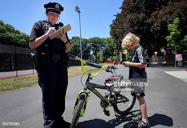 Brookline police officer Katie McCabe left gives a conehead citations to Sebastian Levi for using a helmet while riding his bicycle at Jean B...