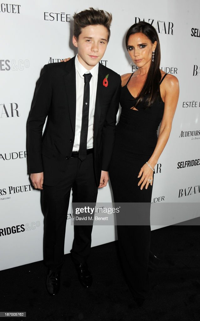 Brooklyn Beckham (L) and Victoria Beckham arrive at the Harper's Bazaar Women of the Year awards at Claridge's Hotel on November 5, 2013 in London, England.