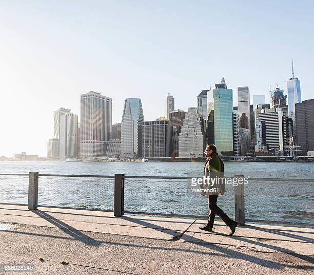 USA, Brooklyn, businessman with briefcase walking in front of Manhattan skyline