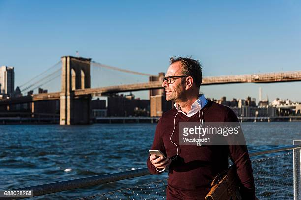 USA, Brooklyn, businessman with smartphone in front of Brooklyn Bridge