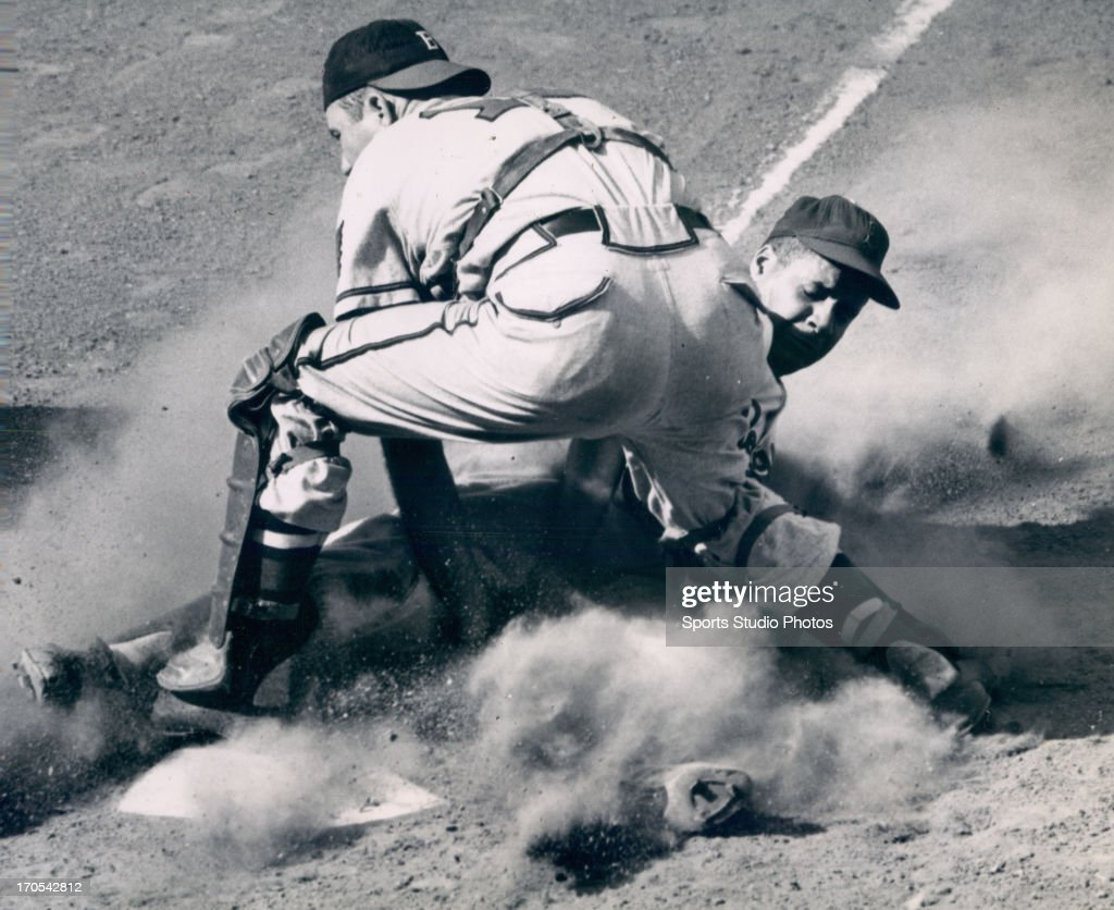 Brooklyn Dodger Ray Campanella sliding into home base past Boston Brave Mickey Livingston.