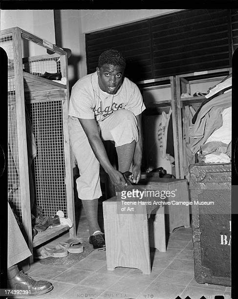 Brooklyn Dodgers baseball player Jackie Robinson tying spikes in locker room Pittsburgh Pennsylvania c 1947