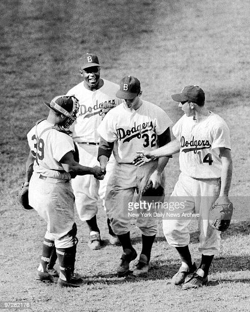 Brooklyn Dodgers catcher Roy Campanella Jackie Robinson and Gil Hodges rush to shake bonus pitcher Sandy Koufax' hand after 19yearold mowed down...