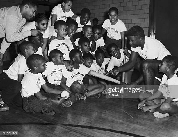 Brooklyn Dodgers Jackie Robinson and Roy Campanella demonstrating some baseball techniques to children at the YMCA in Harlem 17th November 1948