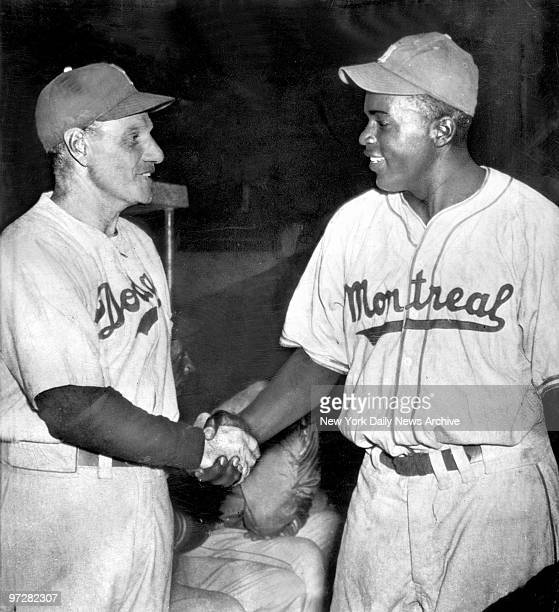 Brooklyn Dodgers' manager Leo Durocher shakes hands with Jackie Robinson in Havana before the Dodgers played Montreal