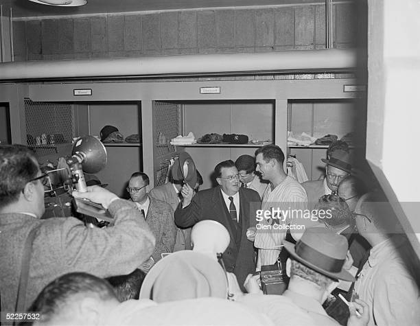 Brooklyn Dodgers owner Walter O'Malley congratulates pitcher Don Larsen of the New York Yankees in the clubhouse at Yankee Stadium after Larsen...