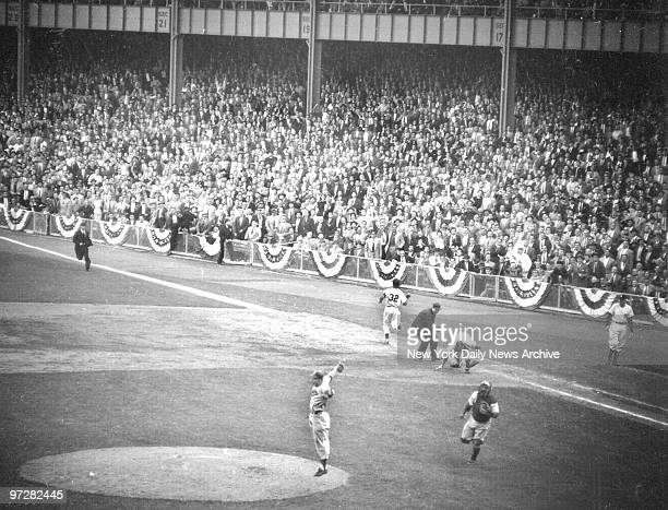 Brooklyn Dodgers players celebrate as New York Yankees' Elston Howard is retired for the last out in the Dodgers' victory over the New York Yankees...