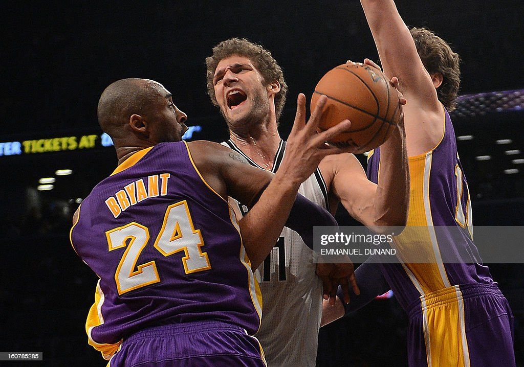 Brooklyn Nets Brook Lopez attempts to go through Los Angeles Lakers Kobe Bryant (L) and Pau Gasol during their NBA game at the Barclays Center in the Brooklyn borough of New York City, February 5, 2013. AFP PHOTO/Emmanuel Dunand