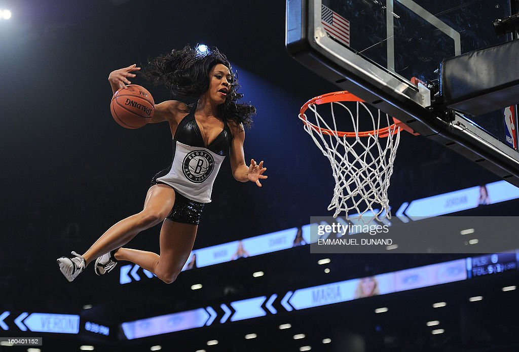 A Brooklyn Nets cheerleader slam dunks a ball during a break while entertaining the crowd during the Nets's game against the Miami Heat during their NBA game at the Barclays Center in the Brooklyn borough of New York City, January 30 , 2013 . AFP PHOTO/Emmanuel Dunand