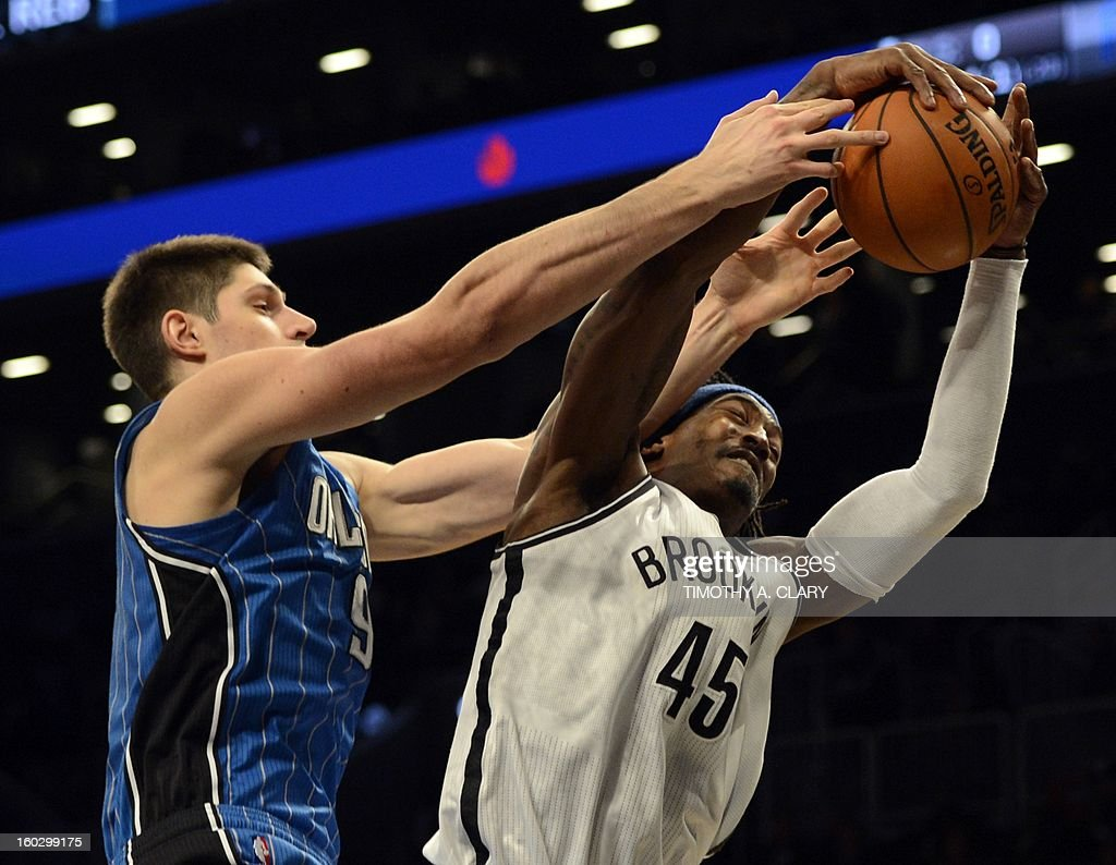 Brooklyn Nets Gerald Wallace (R) goes for rebound with Orlando Magic Nikola Vucevic (L) during their NBA game at the Barclays Center on January 28 , 2013 in the Brooklyn borough of New York City. AFP PHOTO / TIMOTHY A. CLARY