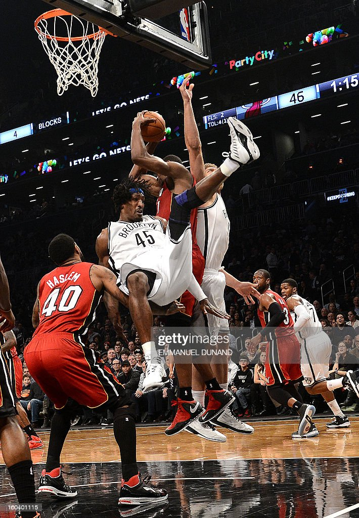 Brooklyn Nets' Gerald Wallace (C) is blocked by Miami Heat's Chris Bosh during their NBA game at the Barclays Center in the Brooklyn borough of New York City, January 30 , 2013 . AFP PHOTO/Emmanuel Dunand