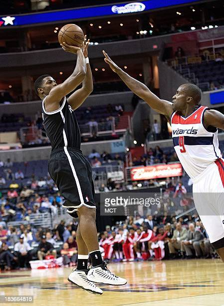 Brooklyn Nets shooting guard Joe Johnson shoots over Washington Wizards small forward Martell Webster during the first half of their preseason game...