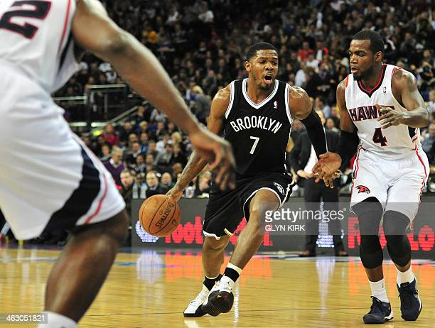 Brooklyn Nets' US player Joe Johnson tries to pass Atlanta Hawks' US player Paul Millsap during the NBA Global Games London 2014 basketball match...