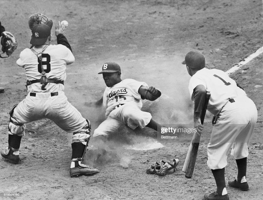 Brooklyn Sandy Amoros slides safely home on Gilliam's double in the third inning of the fourth World Series game at Ebbets Field The ball may be seen...