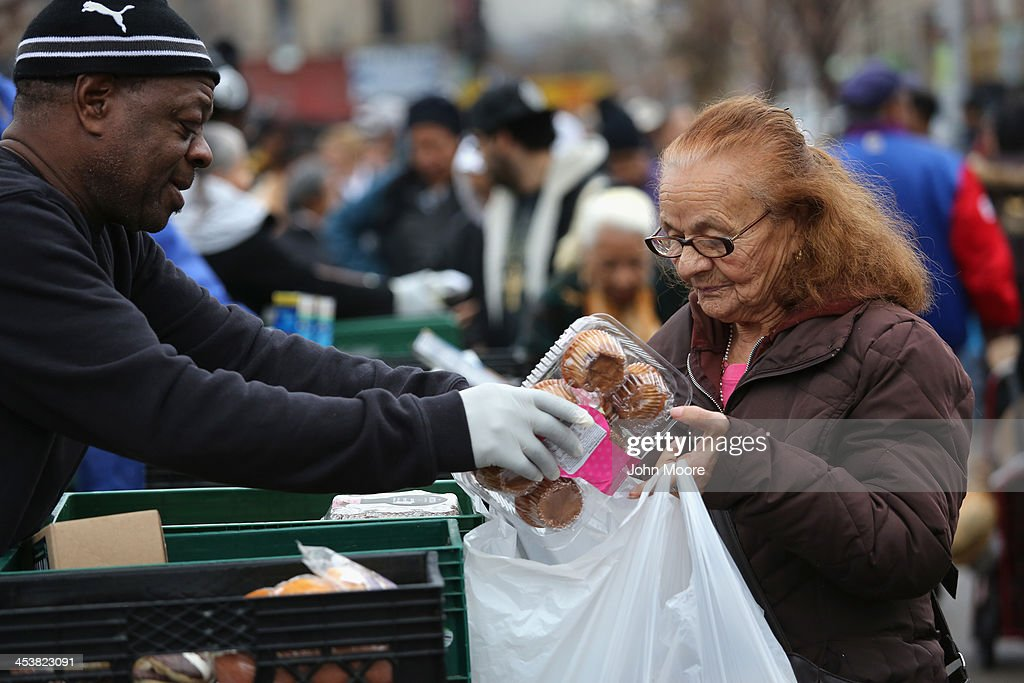 Brooklyn residents receive free food as part of a Bowery Mission outreach program on December 5, 2013 in the Brooklyn borough of New York City. The Christan ministry says it have seen a spike in need since food stamps to low-income families were reduced in November with cuts to the federal Supplemental Nutrition Assistance Program (SNAP).
