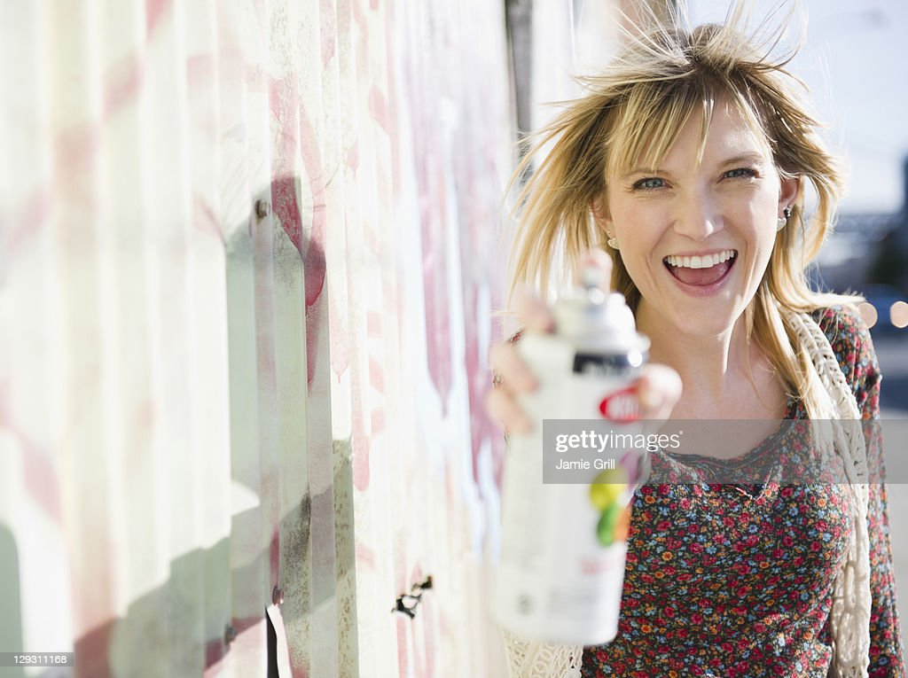 USA, Brooklyn, Williamsburg, Woman spraying with paint can