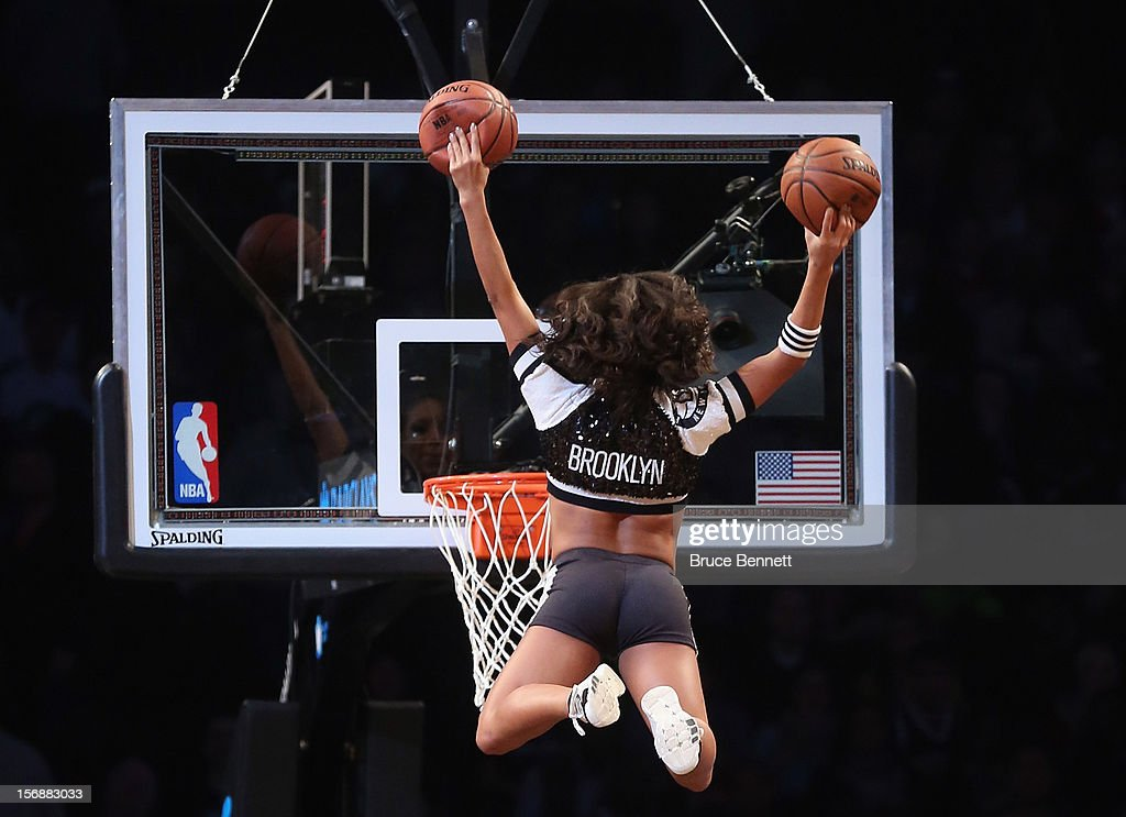 A Brooklynette cheerleader flies in to score two during a break in the game between the Brooklyn Nets and the Los Angeles Clippers at the Barclays Center on November 23, 2012 in the Brooklyn borough of New York City.