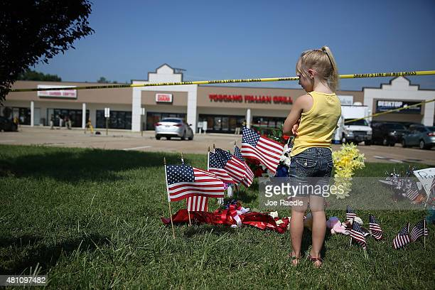 Brooklynn Crawford pays her respects to those killed while visiting a memorial placed in front of the Armed Forces Career Center/National Guard...