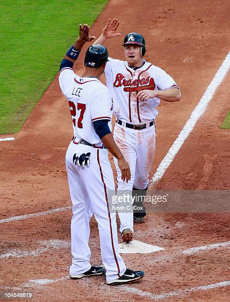 Brooks Conrad of the Atlanta Braves celebrates with Derrek Lee after hitting a threerun homer in the third inning against the Florida Marlins at...
