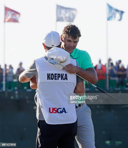 Brooks Koepka of the United States and caddie Richard Elliott react after finishing on the 18th green during the final round of the 2017 US Open at...